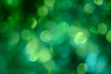 Bokeh. Holiday background. Christmas lights. Glitter. Defocused sparkles. New Year backdrop. Festive wallpaper. Blinks. Carnival. Tinsel. Bokeh retro style photo. Green. Фото со стока