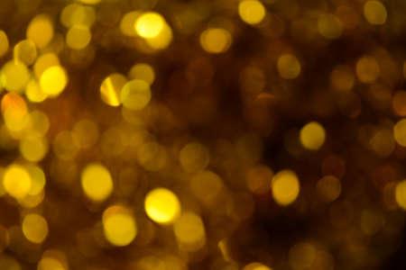 Bokeh. Holiday background. Christmas lights. Glitter. Defocused sparkles. New Year backdrop. Festive wallpaper. Blinks. Carnival. Tinsel. Bokeh retro style photo. Golden. Gold. Фото со стока - 150295997