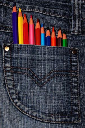 Pencil crayons in a dennim pocket Stock Photo
