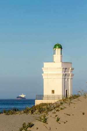 Symbolic lighthouse with boat in background Stock Photo