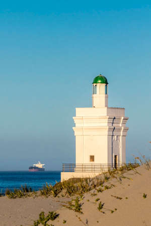 Lighthouse with ship in background Stock Photo