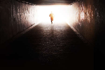 getting away from it all: Man running through the tunnel in the sun