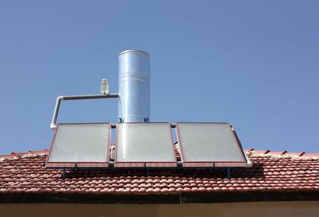 Solar water heating panel on a  roof Stock Photo