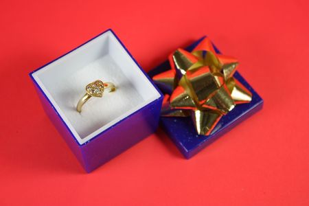 Heart shaped ring in a blue jewelry box on red background photo