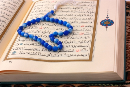 allah: The Holy Koran page with blue rosary