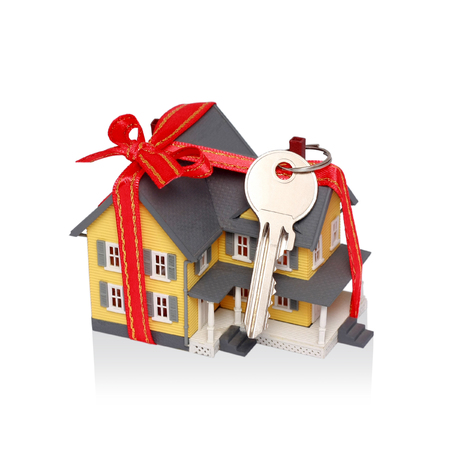 miniatures: Gift miniature house with red ribbon and key isolated on white background  Stock Photo