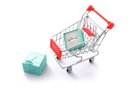 Gift diamond ring in shopping cart isolated on white. Shopping for valentines concept photo