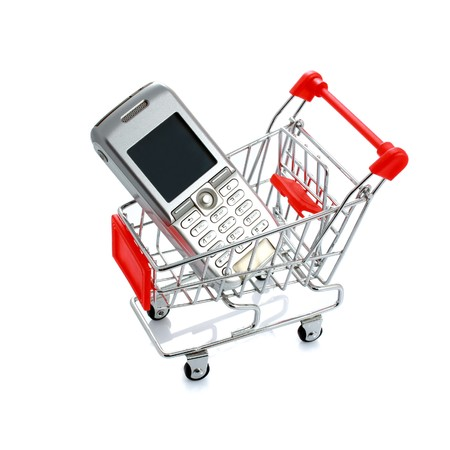 Cell phone in shopping cart isolated on white photo