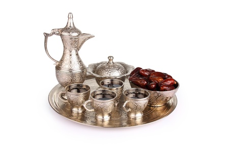 Antique silver pitcher and coffee cup set with dates in a tray isolated on a white background  Including clipping path  photo