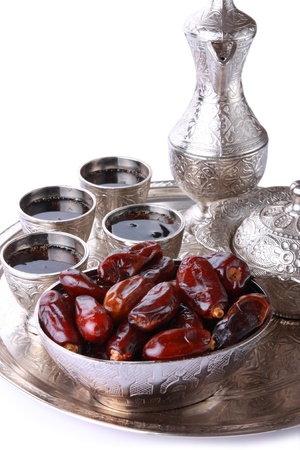 arabic coffee: Antique silver pitcher and coffee cup set with dates in a tray isolated on a white background - vertical  Including clipping path  Stock Photo