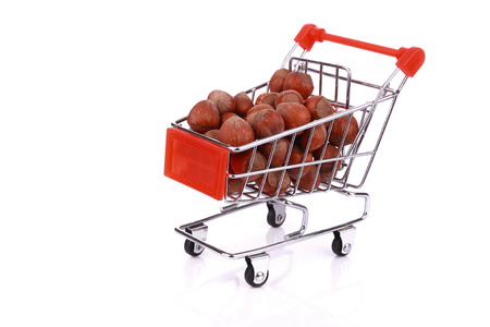 Nuts in miniature shopping cart isolated on white background Stock Photo