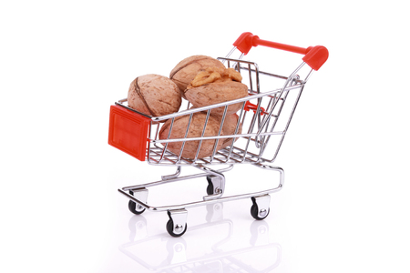 Walnuts in miniature shopping cart isolated on white background Stock Photo
