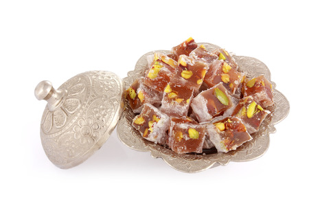 delight: Turkish delights with pistachio nut in a metal sugar bowl isolated on white background