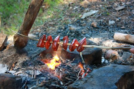 Roasting sausages on fire in nature