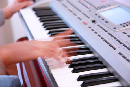 Close up of the hands of a man playing electronic keyboard or piano horizontal