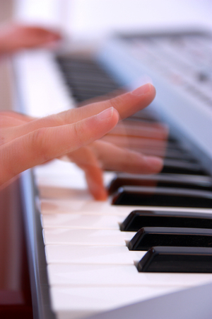 Close up of the hands of a man playing electronic keyboard or piano vertical