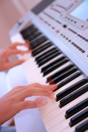 Close up of the hands of a man playing electronic keyboard or piano diagonal angle shot
