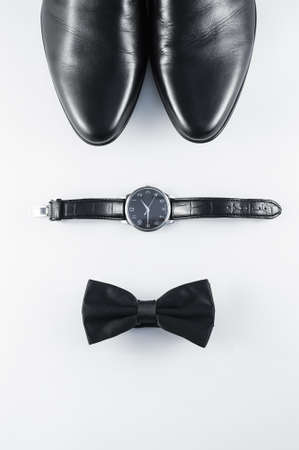 clock face: Black and white minimalistic composition: mens shoes, watches, and the bow tie on a white background. Top view.