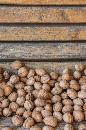 ヴィンテージの木製の背景の多くのクルミ。秋の組成 写真素材