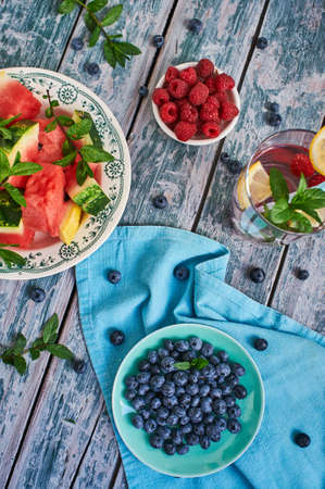 スイカとベリー青いテーブル クロスと古い木のボウル。夏の組成物。青色のトーン