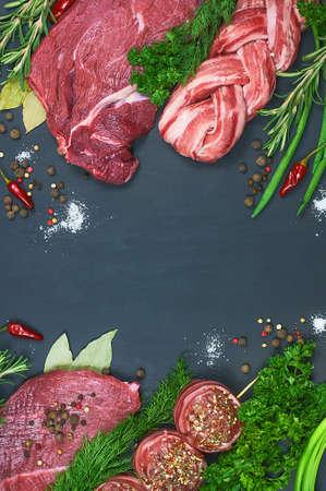 肉の種類。新鮮な肉屋は、暗い背景に肉の品揃えをカットしました。野菜とスパイスを取り入れた。平面図です。クローズ アップ 写真素材