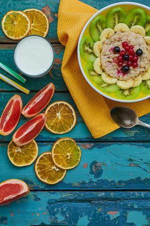 オートミールと果物の健康的な朝食。キウイ、バナナ、ベリー、グレープ フルーツとミルクのガラスとグラノーラ。木製の背景。平面図です。選択 写真素材