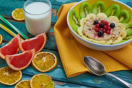 オートミールと果物の健康的な朝食。キウイ、バナナ、ベリー、グレープ フルーツとミルクのガラスとグラノーラ。木製の背景。選択と集中 写真素材