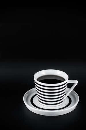 背景の黒のストライプのカップで温かい飲み物。黒と白のミニマルな構成