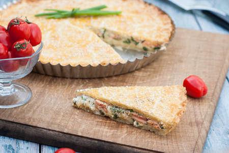 小さめのボウルにプチトマトと食欲をそそる円キッシュ ロレーヌ。新鮮な有機トマト。古いボードとして様式化された青色の背景