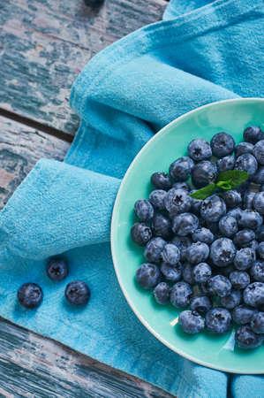 青いテーブル クロスと古い木のボウルに果実。夏の組成 写真素材