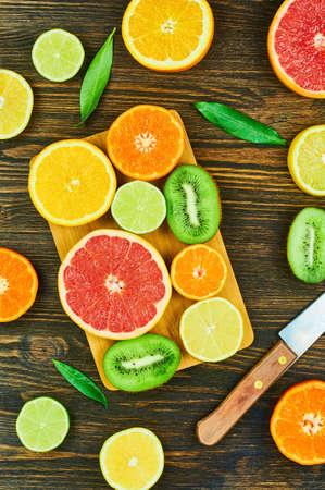 果物をスライスします。オレンジ、ライム、グレープ フルーツ、みかん、梨、キウイ、レモン。コピー スペースと木のテーブル背景。トップ ビュ 写真素材