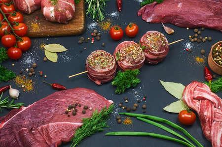 肉の種類。新鮮な肉屋は、暗い背景に肉の品揃えをカットしました。野菜とスパイスを取り入れた。クローズ アップ