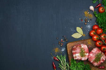 木製のまな板に生の肉。野菜とスパイスを取り入れた。暗い背景。トップ ビュー