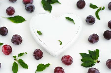 白の木製心臓と白地に熟したジューシーなプラム