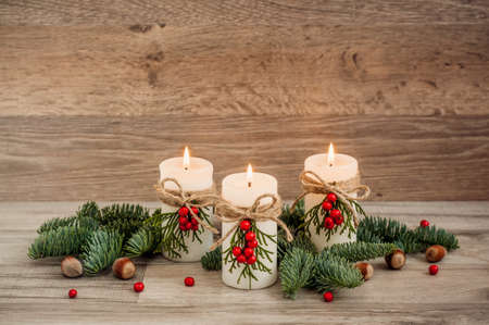クリスマスの飾り: 3 つの燃焼のキャンドル、モミ、山の灰、ヘーゼル ナッツ。木製の背景。