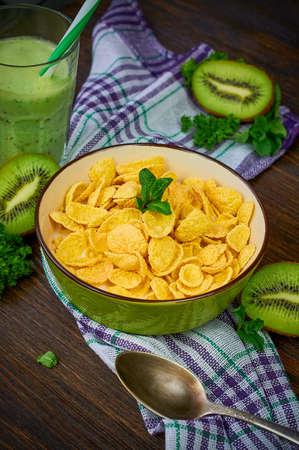 キウイのスムージーとコーンフレーク。コーンフレーク、新鮮なフルーツ、キウイは、木製の背景にデトックスします。クローズ アップ。選択と集