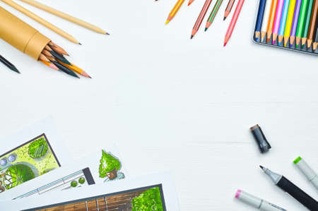 tabletop: Top view of workplace of a designer with copyspace. Sketching tools: liners, markers, sketch images and pencils on a creative tabletop. Place for text