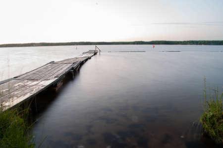 long lake: footbridge on the lake at sunset, long exposure, low waves