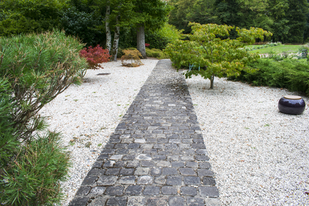 Landscaping, good work of professional landscaper, stone paved path lined with pebbles surrounded by shrubs, path leading to the garden with flowers and further the forest of the park
