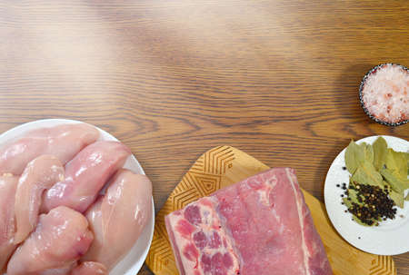 A piece of raw pork and chicken on a cutting board, a white saucer with bay leaves, pepper and spices, a bowl of salt. Blank space for menu text, recipe, ingredients.