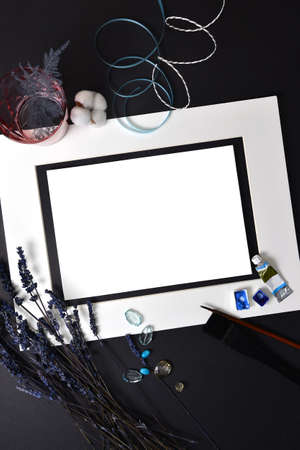 Background flatlay white frame and a sheet of paper on a black sheet with decor. Pink glass cup, cotton, ribbons, lavender sprigs, beads, brushes, watercolor paints. Mockup, empty space for text.