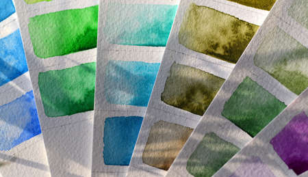 Color palette close-up watercolor on white paper, green and blue shades. Sunlight falls on the paper, shadows from plant leaves, beautiful paint streaks, granulation.