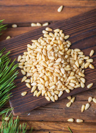 Peeled pine nuts are heaped on a dark wooden cutting board. In the background, sprawling branches of a green pine tree. View from above.