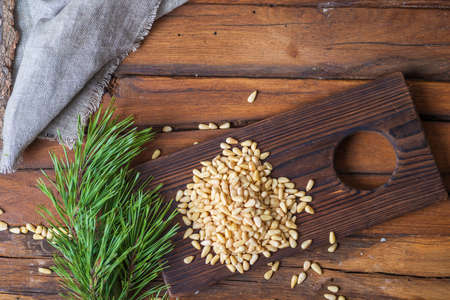 Pine nuts are heaped on a cutting board. On the table next to it is a pine branch with green needles and a gray rough cloth. Top view, background with diet food, blank space for a recipe. Foto de archivo