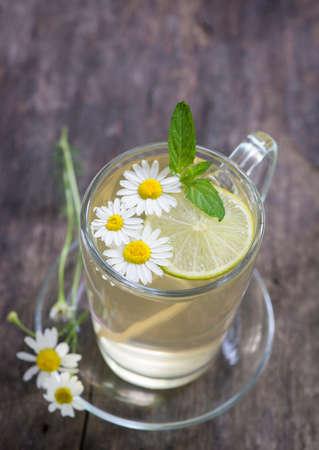 chamomile tea: Chamomile tea and flowers on wood background