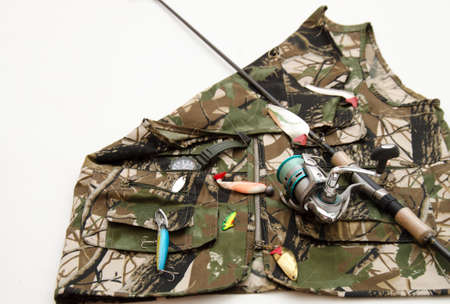 hand line fishing: Rod with reel and fishing accesories on camouflage jacket isolated on white background