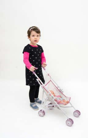 niño empujando: Adorable niña de dar un paseo a su muñeca en un pequeño cochecito aislado en fondo blanco