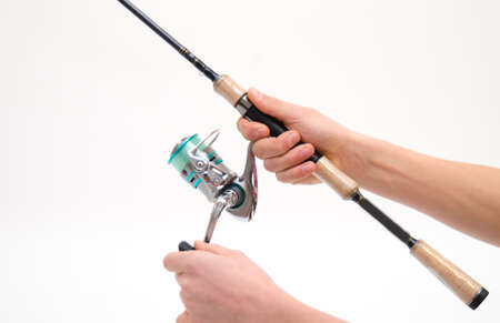 hand line fishing: Rod with reel in hand isolated on white background