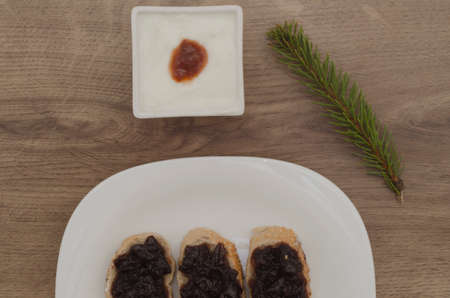 Jam on slices of bread and yogurt and pin leaves on wood background photo