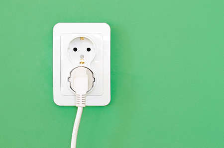 grounded plug: European white electrical outlet socket and white cable pluged in isolated on green wall Stock Photo